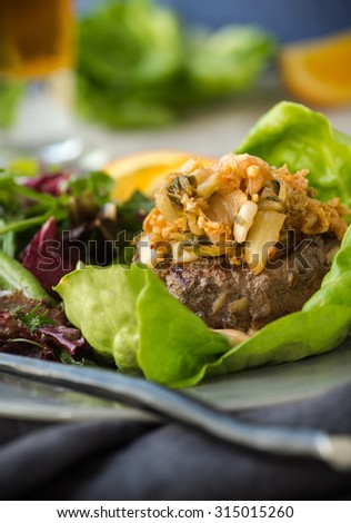 Delicious and spicy beef burger with mixed green salad - stock photo