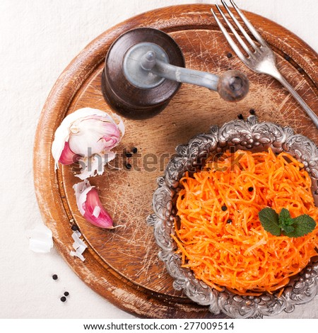 Delicious and spicy carrot spaghetti with ginger, garlic, chilli and olive oil on round chopping board. Top view.  - stock photo