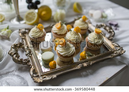 Delicious and tasty dessert table at wedding reception macaroons and cupcakes - stock photo
