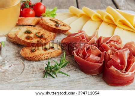 delicious appetizer to wine - ham,prosciutto, cheese, capers, tomato, served on a light wooden board - stock photo