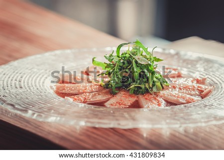 Delicious appetizer with herbs on glass plate on wooden table - stock photo