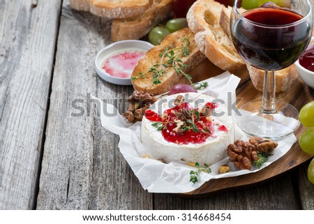 delicious appetizers - camembert with berry jam, toast and grapes, close-up