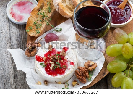 delicious appetizers for wine - camembert, berry jam, toast and fresh grapes, top view