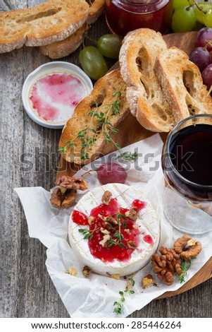 delicious appetizers for wine - camembert, berry jam, toast and fruit, vertical, top view, close-up - stock photo