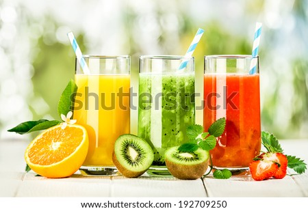 Delicious array of fresh fruit juices served in tall glasses made from liquidised orange, kiwifruit with peppermint, and strawberries for healthy summer treats rich in vitamins - stock photo