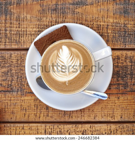 delicious art capuccino coffee cup on wooden background - stock photo