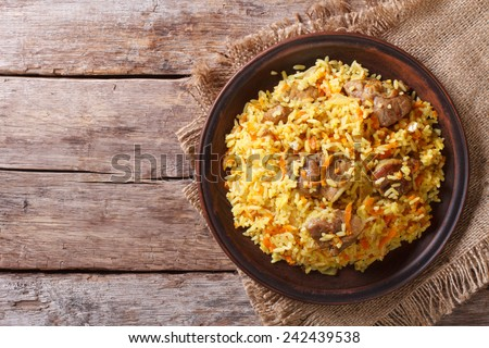 Delicious Asian pilaf on a brown plate. horizontal view from above, rustic style  - stock photo