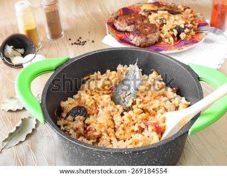 Delicious asian rice with carrot and dried fruits in the pan. Beef meatballs with garnish served on a color plate and various spices in the blurred background. Homemade cooking. Selective focus  - stock photo
