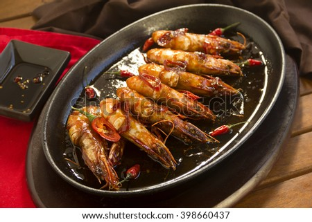 Delicious Asian sizzling chilli shrimps served in a hot cast iron platter.