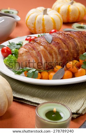 Delicious bacon-wrapped turkey breast roulade garnished with Brussels sprouts, tomatoes, and Parisian carrots.