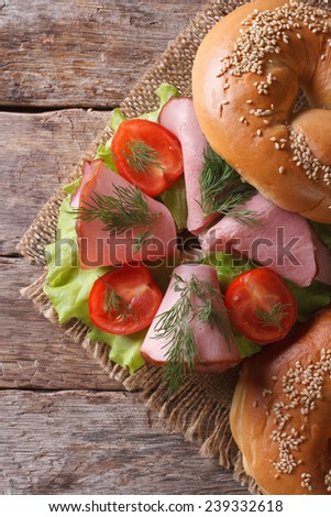 delicious bagel with ham and vegetables on wooden table close-up. top view of the vertical  - stock photo