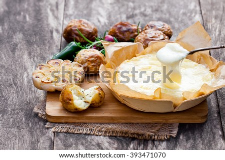 Delicious  baked camembert with roasted potato and garlic  - stock photo