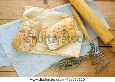 Delicious baked pies with meat on a wooden background in rustic style