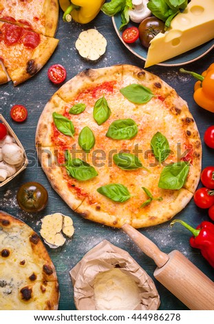 Delicious baked pizza and ingredients for making pizza. Flour, cheese, tomatoes, basil, pepperoni, mushrooms and rolling pin over wooden background. Top view. Pizza ready to eat - stock photo