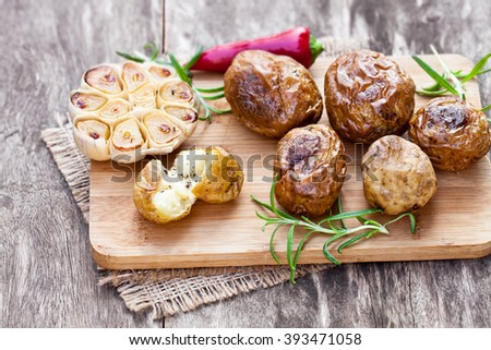 Delicious  baked potato and garlic with chili pepper and rosemary   - stock photo