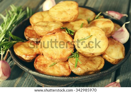 Delicious baked potato with rosemary in frying pan on table close up - stock photo