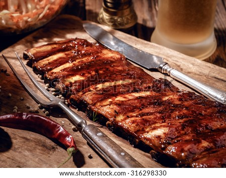 Delicious BBQ ribs with coleslaw and beer on wooden table. - stock photo