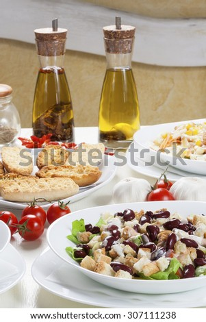 Delicious bean salad with various vegetables and toast bread arranged on the white table with fresh garlic, tomatoes and two bottles with spicy edible oil. - stock photo