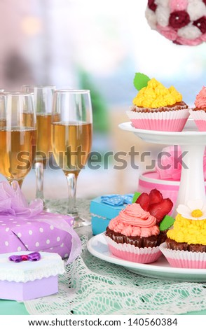 Delicious beautiful  cupcakes on festive table on room background