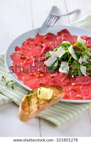 Delicious beef carpaccio with rocket salad, parmesan cheese and roasted pine nuts, served with a slice of toasted baguette with a butter roll - stock photo