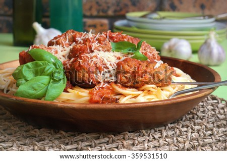 delicious beef meatballs with a basil and garlic tomato sauce on a top of spaghetti. selective focus - stock photo