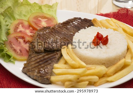 Delicious beef steak dinner with french fries tomatoes.