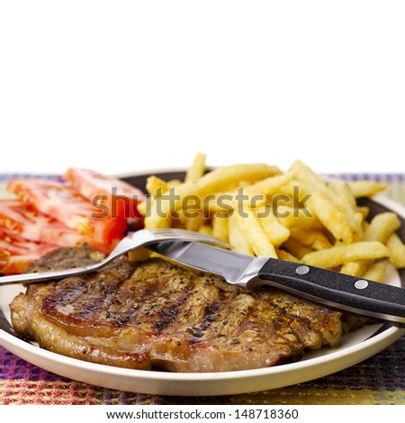 Delicious beef steak dinner with french fries tomatoes and utensils on plate against white background. - stock photo