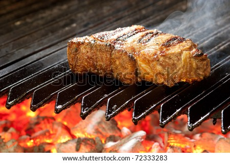 Delicious beef steak, hot barbecue grill.