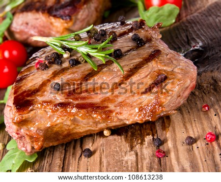 Delicious beef steak on wooden planks - stock photo