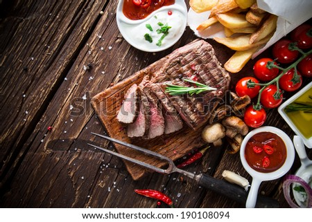 Delicious beef steak on wooden table, close-up - stock photo