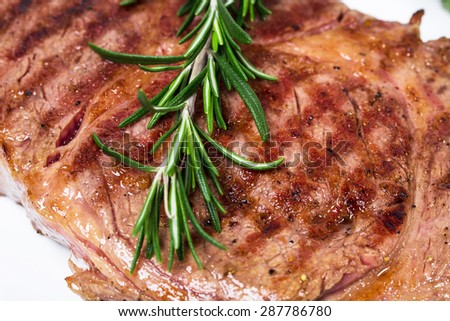 Delicious beef steak with grilled asparagus and rosemary bunch. Macro. Photo can be used as a whole background. - stock photo