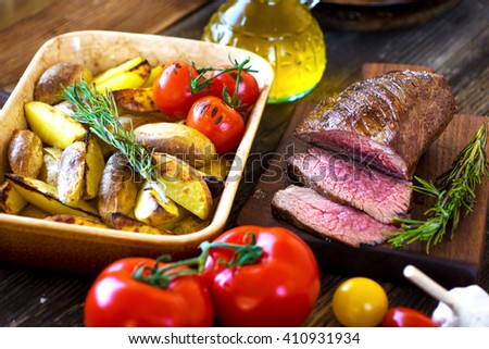 Delicious beef steak with potato on wooden background. - stock photo