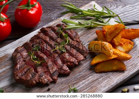 Delicious beef steak with tomato. Meat and rosemary on wooden background. - stock photo