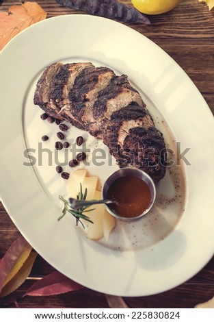 Delicious beef steak with tomato sauce, melon and rosemary, decorated with coffee beans on the plate, wooden table. autumn concept. Selective focus - stock photo