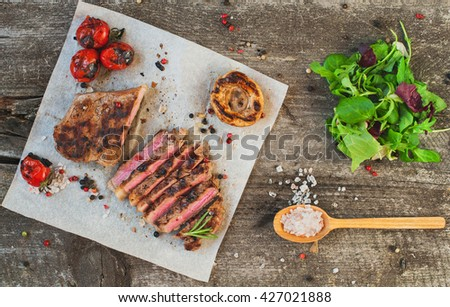 Delicious beef steak with tomatoes on a old wooden board - stock photo