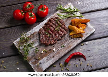 Delicious beef steak with tomatos. Meat and rosemary on wooden background. - stock photo