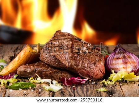 Delicious beef steakes on wood with fire background - stock photo