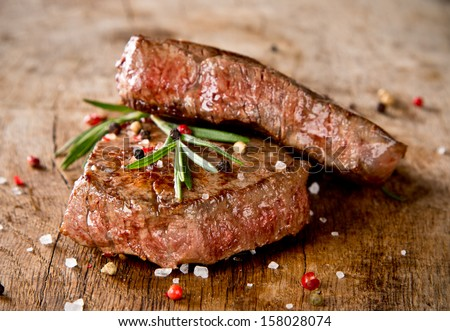 Delicious beef steaks on wood - stock photo