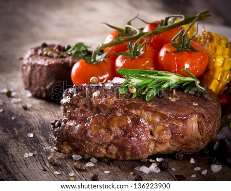 Delicious beef steaks on wooden table - stock photo