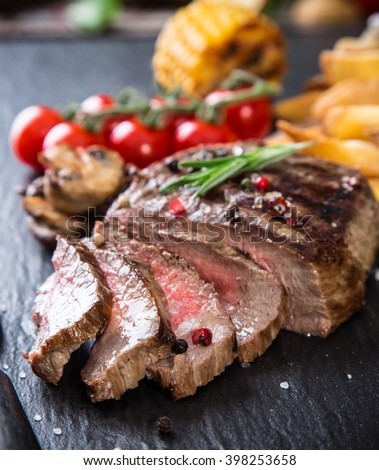 Delicious beef steaks on wooden table, close-up. - stock photo
