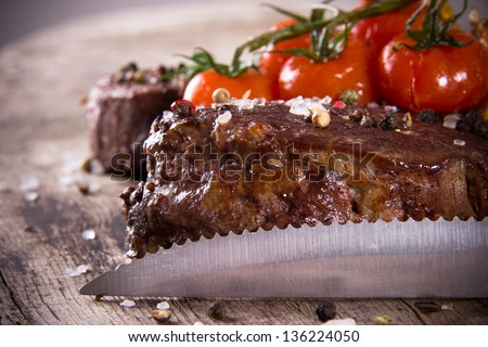 Delicious beef steaks with knife on wooden table - stock photo
