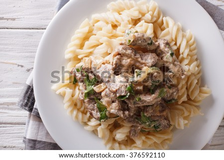 Delicious beef stroganoff with pasta fusilli close-up on a plate on the table. horizontal view from above