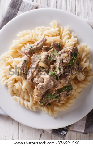 Delicious beef stroganoff with pasta fusilli close-up on a plate on the table. Vertical view from above