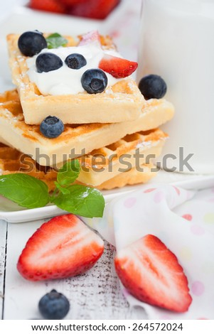 Delicious Belgian waffle with fresh berries and cream for breakfast, white wooden background - stock photo