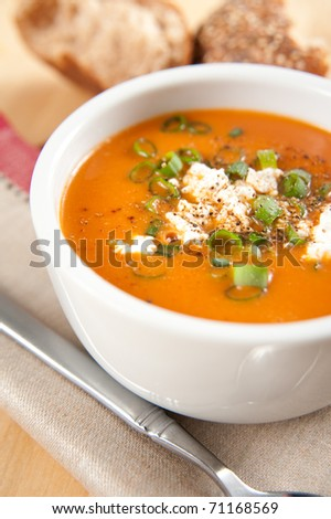 Delicious Bell Pepper and Tomato Creamy Soup with Goat Cheese, Green Onion, plus Whole Grain Bun