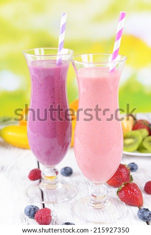 Delicious berry cocktails on table on bright background - stock photo