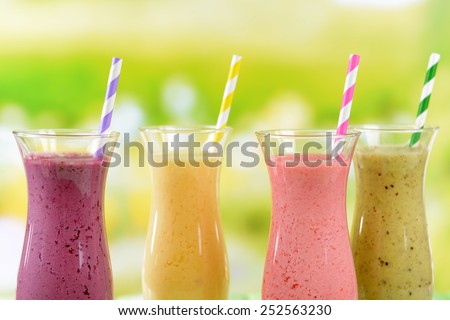 Delicious berry cocktails on table on bright background