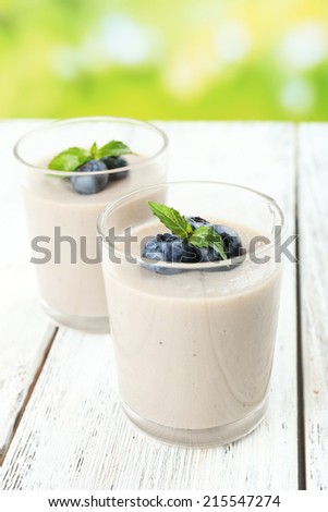 Delicious berry mousse in glasses on table on bright background