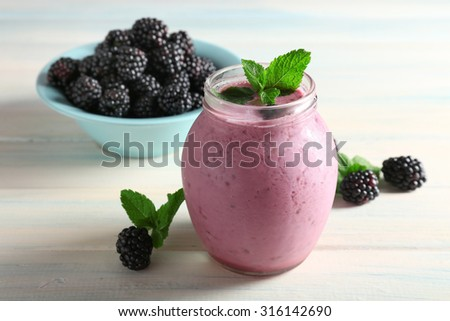 Delicious berry smoothie with blackberries on wooden table close up