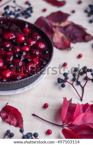 Delicious berry tart with marmalade, raspberry, currant and whipped cream. Randomly lie around wild grape leaves, blue and red berries.